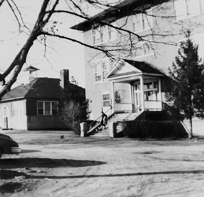Black and white photograph from 1955 showing the two schools at Floris. One is a single-story building with a bell tower on the roof. The second building is much larger with three stories.