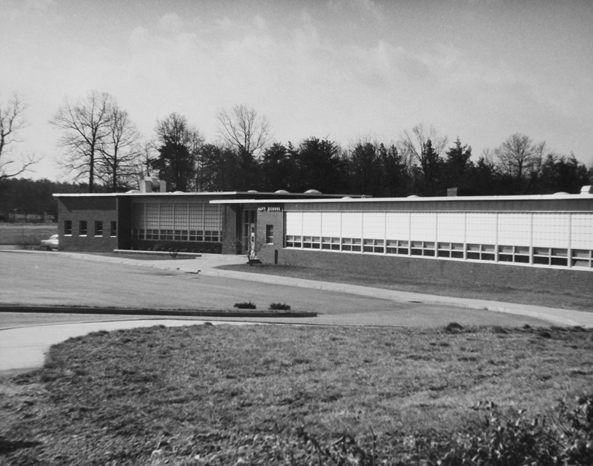Black and white photograph of the front exterior of Navy Elementary School showing the original main entrance to the building.