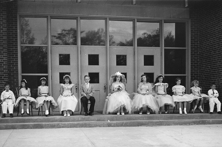 Black and white photograph of the May Day court. The students are posed in front of the original main entrance to Navy Elementary School.