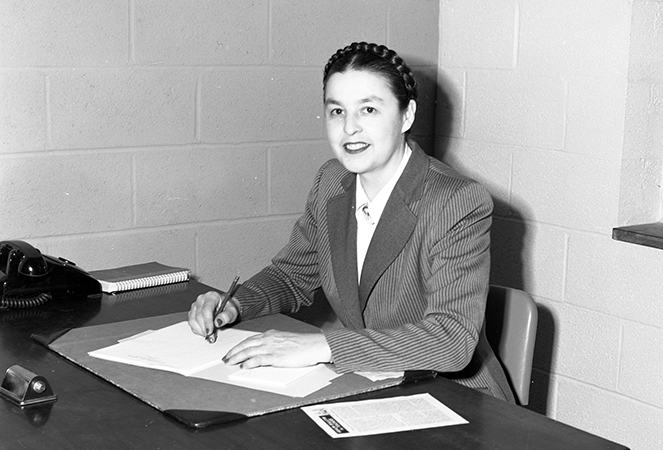 Black and white photograph of Principal Harrison seated at her desk. The walls are unadorned because the school had only recently been completed.