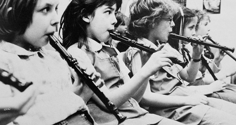 Black and white photograph of students playing recorders.