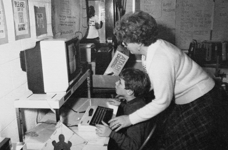 Black and white photograph of a teacher and a student at a computer workstation.