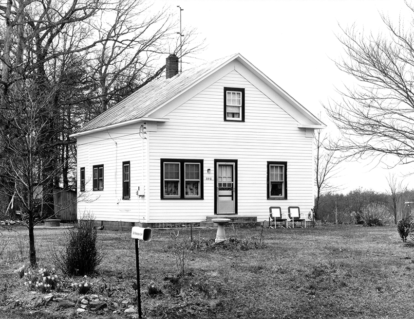 Black and white photograph of a small house with white siding.