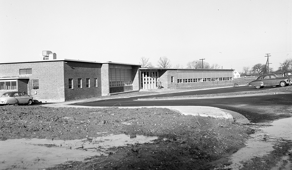 Black and white photograph of the original front entrance of Navy Elementary School. The entrance faced West Ox Road and had a small parking lot in front.